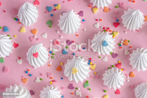 Crispy white twisted meringues and with confectionary decorations on pink background