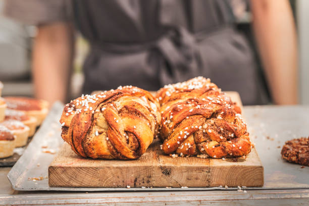 Twisted traditional Swedish cinnamon buns at a café Twisted traditional Swedish cinnamon buns at a café. The sweet buns are on a wooden chopping board, and there is an  unrecognizable person with an apron in the background. sweet bun stock pictures, royalty-free photos & images