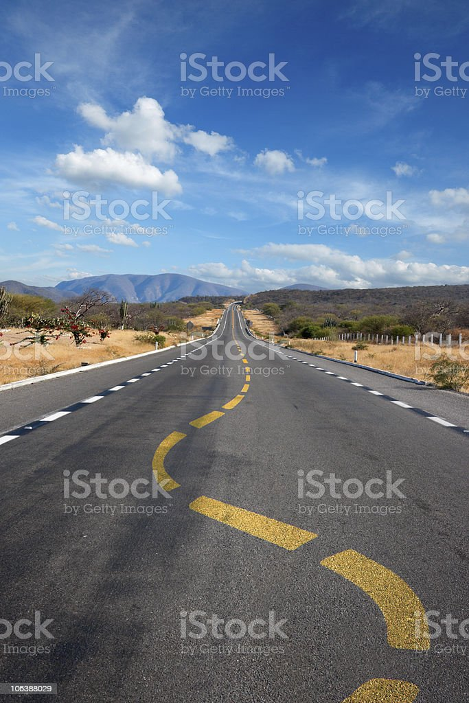 Twisting lane marking on road in desert stock photo