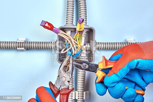 istock Twisting wires with needle-nose pliers. 1138036985