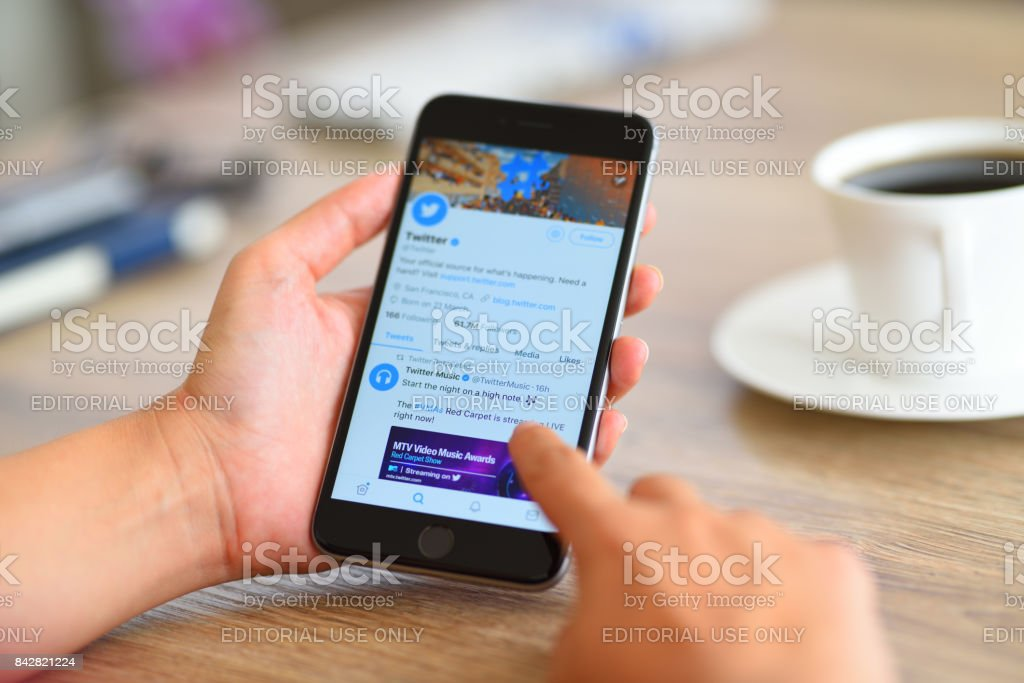 Twitter on Apple iPhone 6 İstanbul, Turkey - August 28, 2017: Woman using smart phone on a wooden desk. The smart phone is an iPhone 6 plus displaying Twitter application.  iPhone is a touchscreen smartphone developed by Apple Inc. Adult Stock Photo