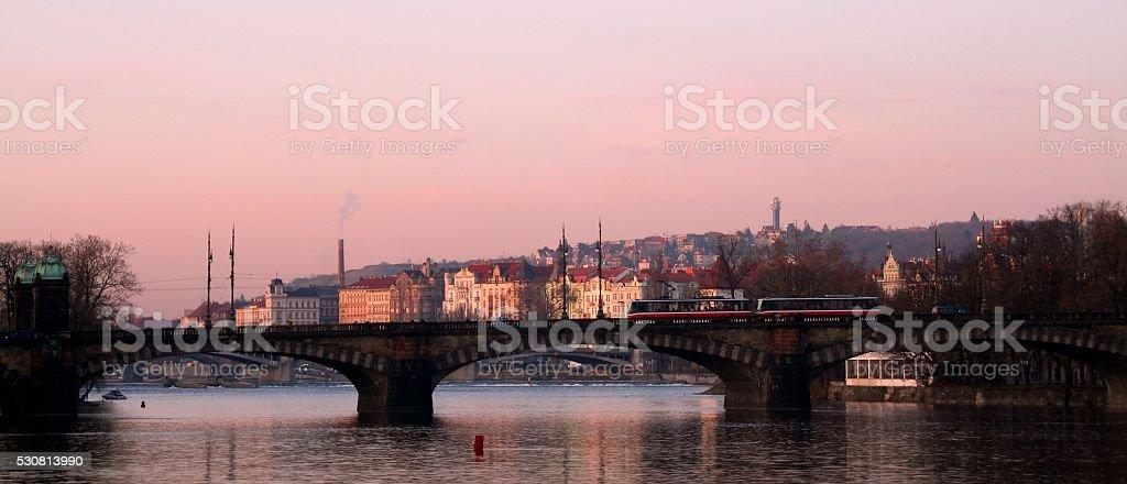 Twlight Prague cityscape bridge Vltava river tram moody sky stock photo