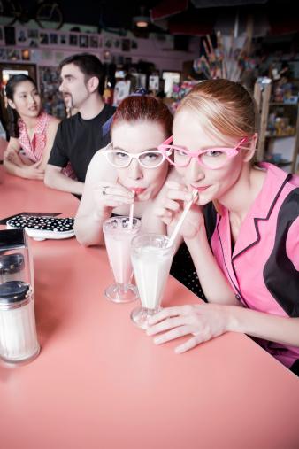 Tow girls drinking milkshakes in a classic diner with their friends.
