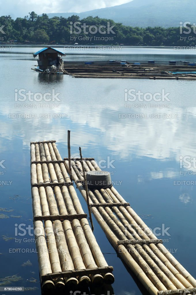 Two 2 bamboo boat rafts anchored at mountain lake shore on a cloudy day stock photo