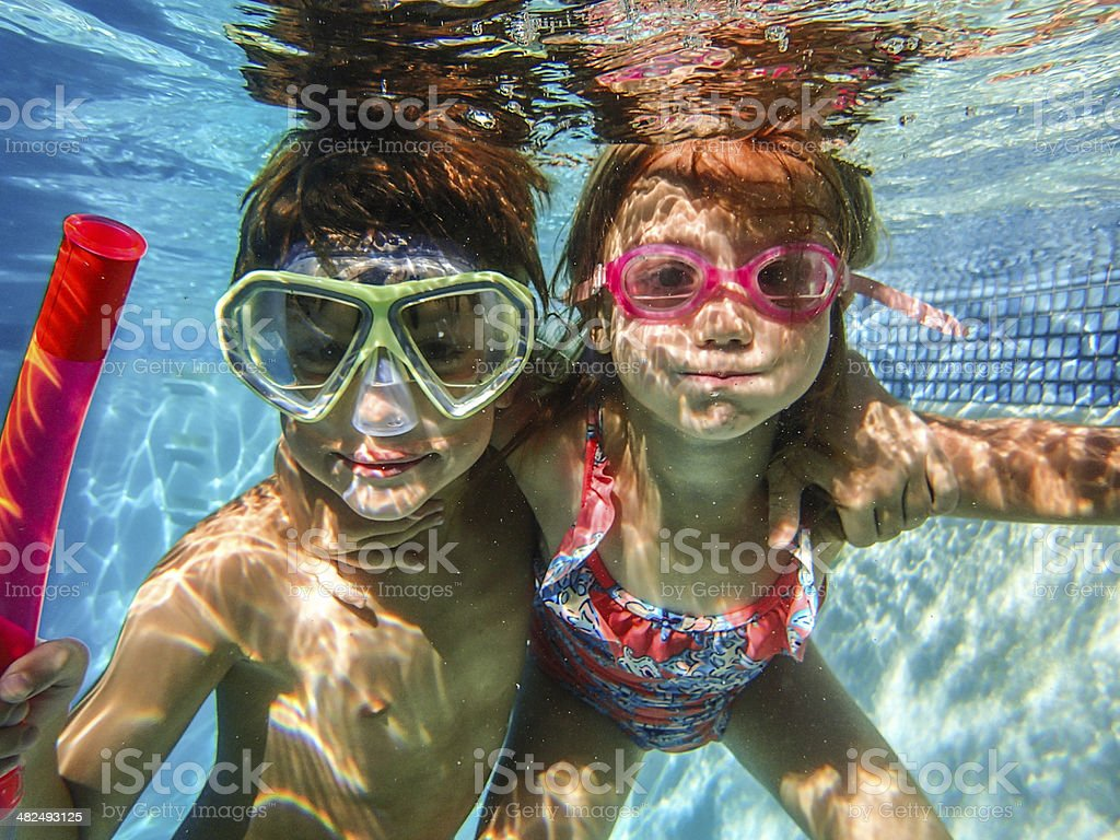 Two 2 happy kids in swimming pool underwater stock photo