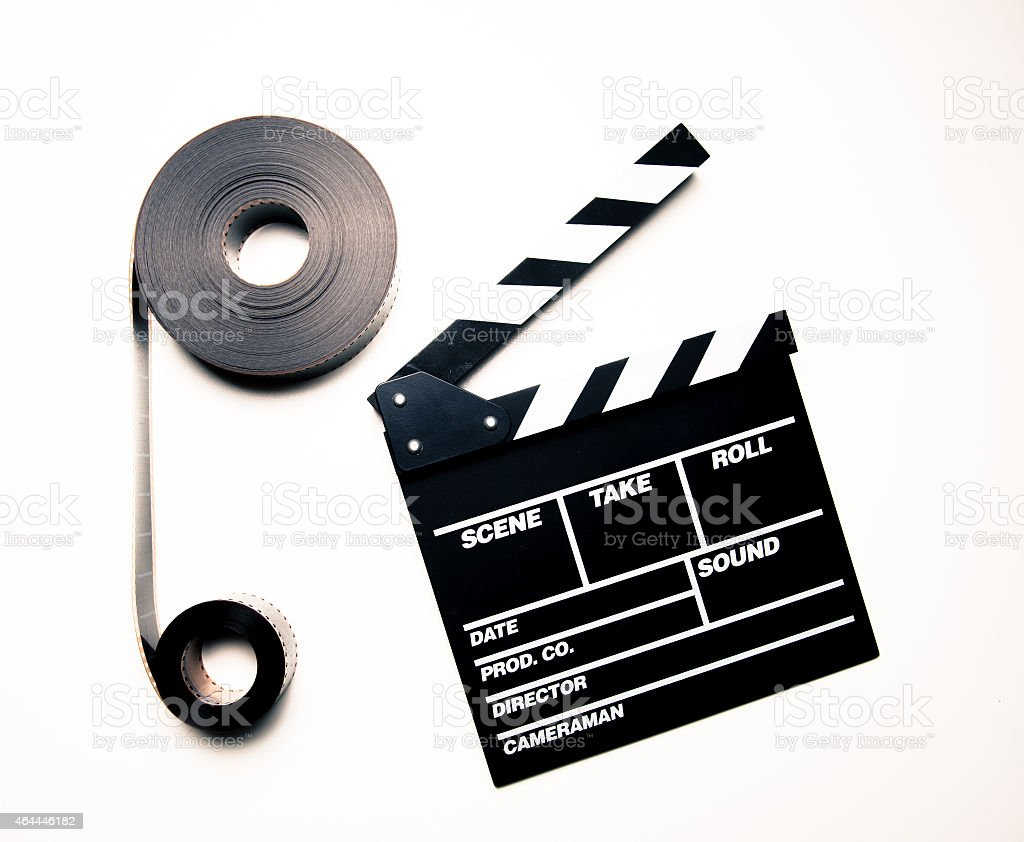 Two 35mm movie reels and clapperboard in vintage color effect stock photo