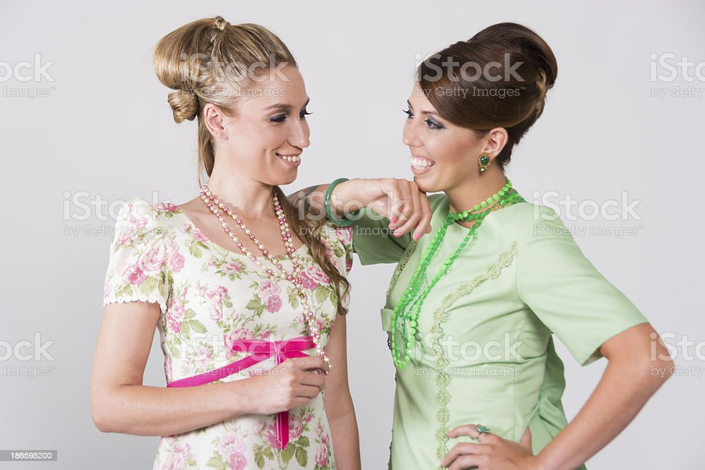 Two 60s styled friends in conversation. stock photo
