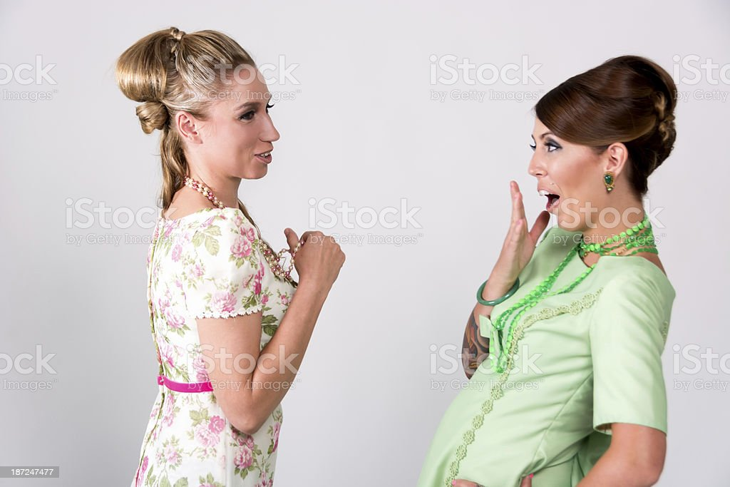 Two 60s styled friends sharing shocking story. stock photo