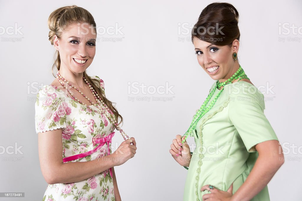 Two 60s styled women playing with necklaces. stock photo