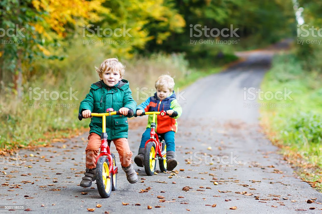 Two active brother boys having fun on bikes in autumn stock photo