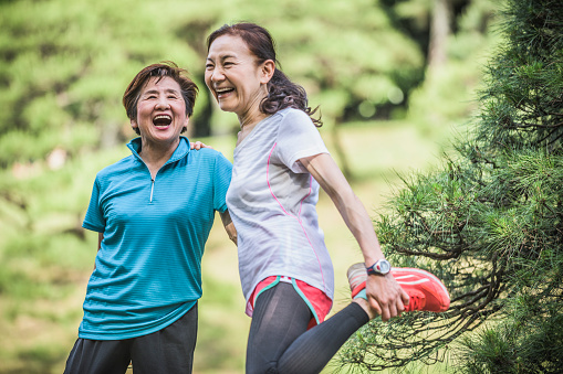 Two senior Asian friends getting ready for a run, one woman is holding her leg and has her hand on her friend's shoulder for support