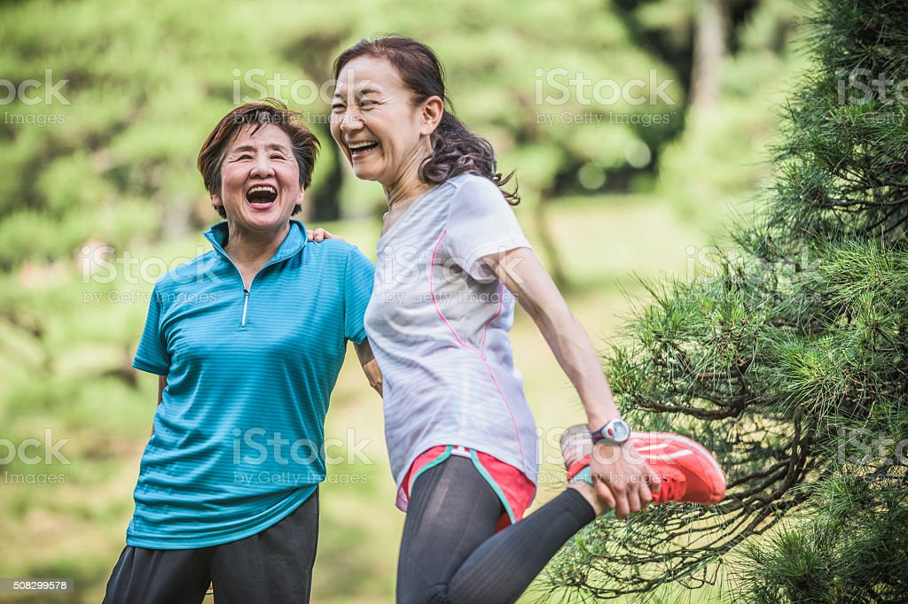 Two active Japanese women laughing, one stretching leg stock photo