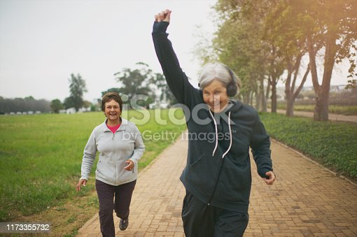 Two senior active Caucasian women running jogging together outdoors positive emotion on a misty morning one woman listening to music on headphones from a mobile phone outside Stellenbosch South Africa