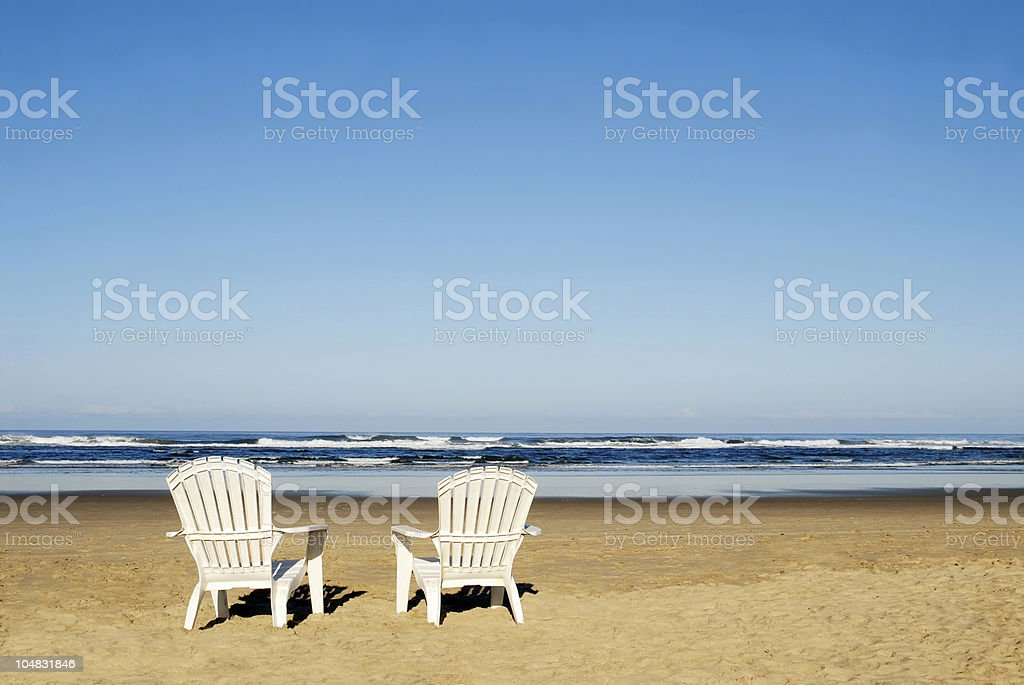 Two Adirondack Chairs On A Beach Stock Photo