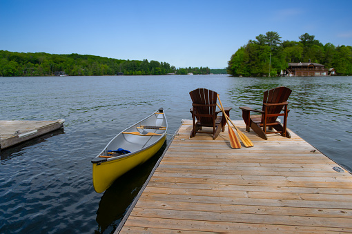 Two Adirondack chairs on a wooden pier facing the blue water of a lake in Muskoka, Ontario Canada. A yellow canoe is tied to the dock while the paddles are next to the chairs.