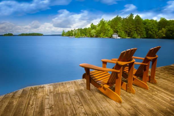 ahşap bir iskelede oturup iki adirondack sandalye - kır evi stok fotoğraflar ve resimler