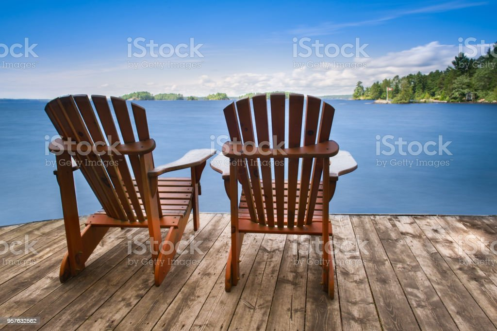 Two Adirondack chairs sitting on a wooden dock stock photo