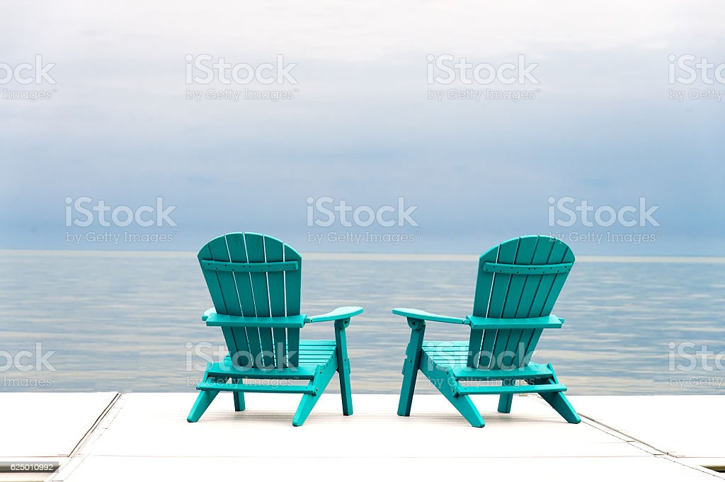 Two Adirondack Muskoka Chairs on the water's edge stock photo