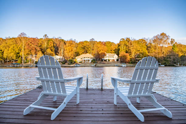 Two Adirondack style chairs on a dock stock photo