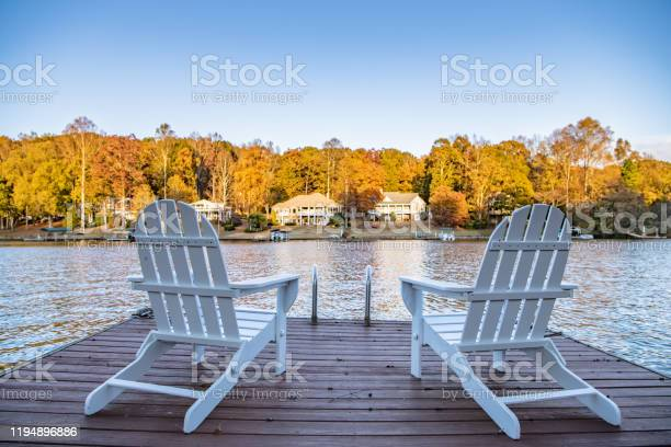 Photo of Two Adirondack style chairs on a dock