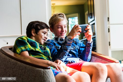 Two boys at home in the living room using a smartphone to surf the internet.
