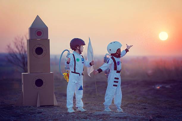 two adorable children, playing in park on sunset - mini amusementpark stockfoto's en -beelden