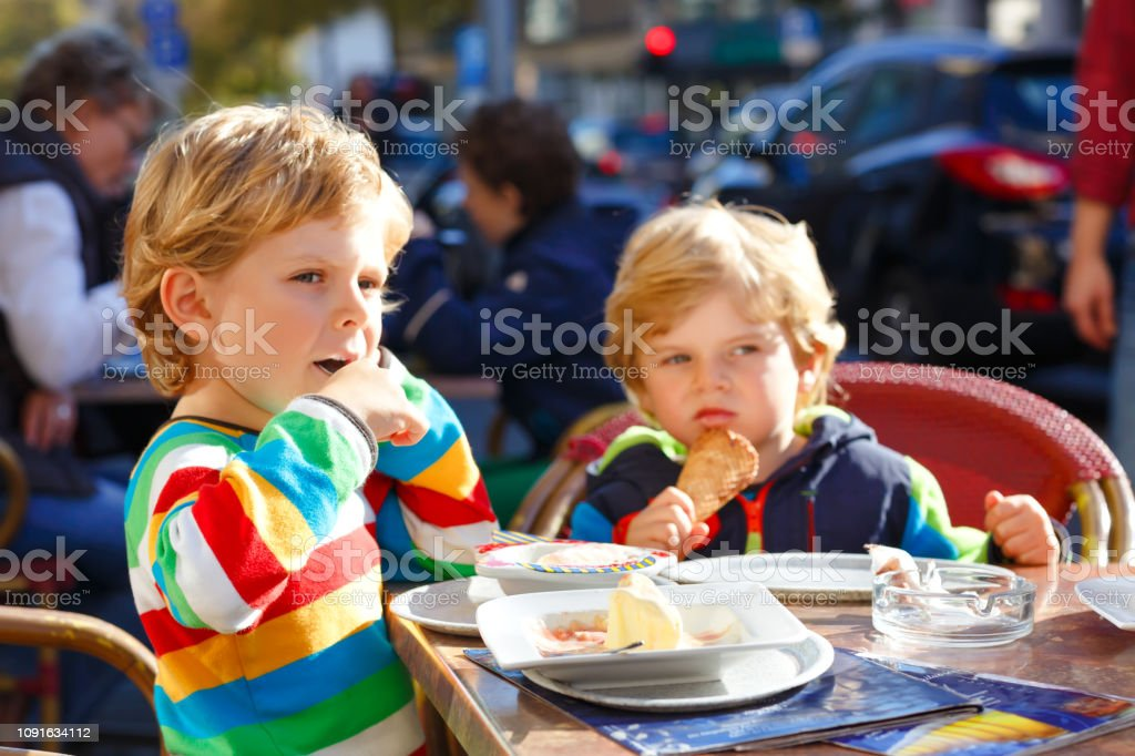 Two adorable kids boys eating ice cream in outdoor cafe. Happy family on sunny day. Healthy children, twins and best friends with sweet dessert in gelateria restaurant