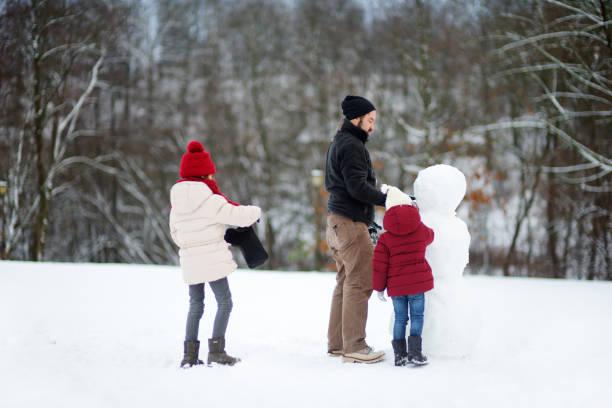 zwei entzückende kleine mädchen bauen einen schneemann zusammen im schönen winter park. nette schwestern spielen im schnee. - schneemann bauen stock-fotos und bilder