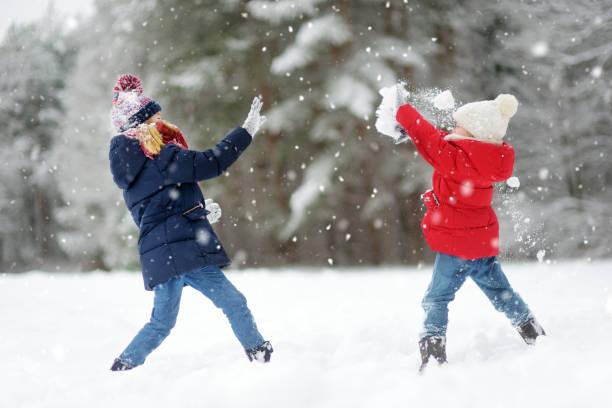 Zwei entzückende kleine Mädchen, die gemeinsam Spaß im schönen Winterpark haben. Schöne Schwestern spielen im Schnee. – Foto