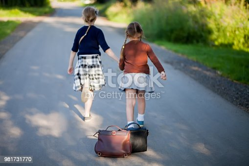 istock Two adorable little girls running home from school 981731770