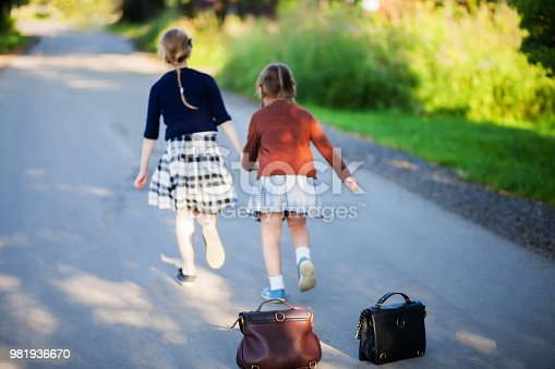 istock Two adorable little girls running home from school 981936670