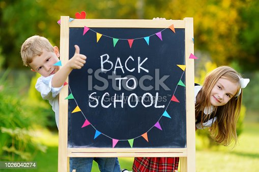 istock Two adorable little schoolkids feeling exited about going back to school 1026040274
