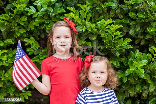 539482224 istock photo Two adorable little sisters holding american flags outdoors on beautiful summer day. Independence Day concept. Patriotic holiday. 4th of July party. Labor day 1158282063
