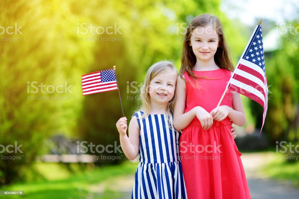 Two adorable little sisters holding american flags outdoors on beautiful summer day Two adorable little sisters holding american flags outdoors on beautiful summer day. Independence Day concept. American Culture Stock Photo