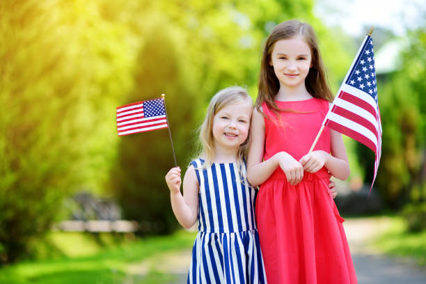 Two adorable little sisters holding american flags outdoors on beautiful summer day Two adorable little sisters holding american flags outdoors on beautiful summer day. Independence Day concept. family 4th of july stock pictures, royalty-free photos & images