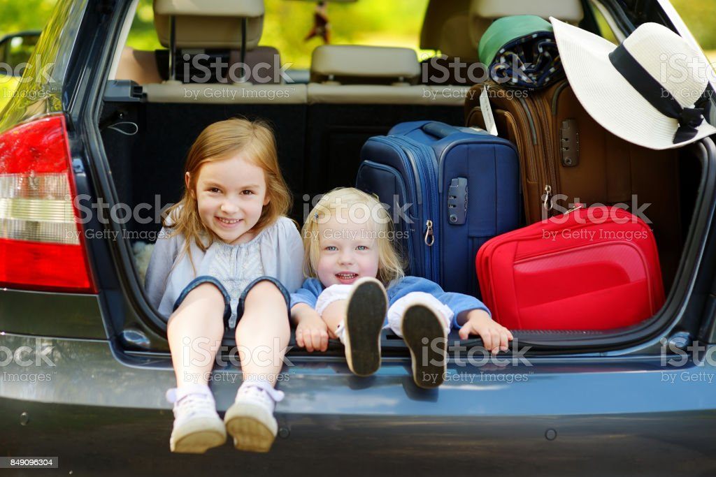 Two adorable little sisters sitting in a car stock photo