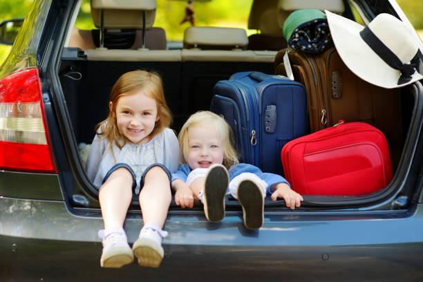 Zwei entzückende kleine Schwestern sitzen in einem Auto – Foto