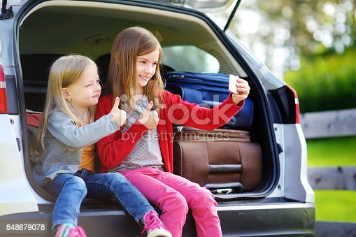 807410214istockphoto Two adorable little sisters taking photo of themself before going on vacations with their parents 848679078
