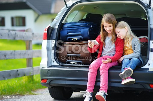 807410214istockphoto Two adorable little sisters taking photo of themselves before going on vacations with their parents 848679132