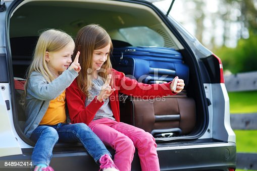 807410214istockphoto Two adorable little sisters taking photo of themselves before going on vacations with their parents 848942414