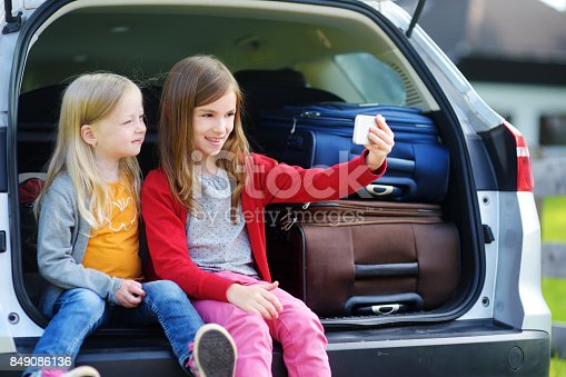 807410214istockphoto Two adorable little sisters taking photo of themselves before going on vacations with their parents 849086136