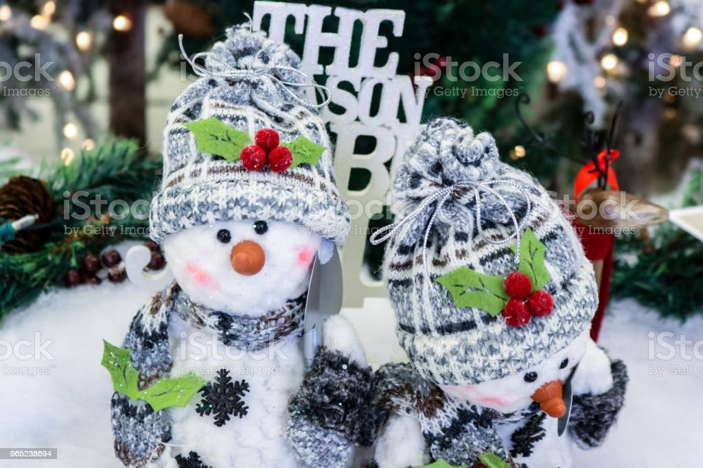 Two adorable ornamental snowmen with snow shovels caps and scarves in front of blurred Christmas background royalty-free stock photo