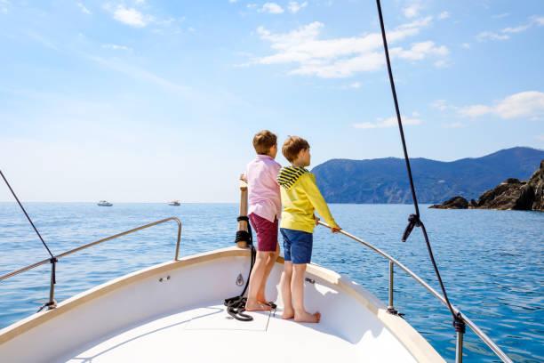 Zwei entzückende Schule Kind Jungs, beste Freunde genießen Segelboot Fahrt. Familienurlaub auf dem Meer an sonnigen Tagen. Kinder lächeln. Brüder, Schulkinder, Geschwister, beste Freunde mit Spaß auf der Yacht. – Foto