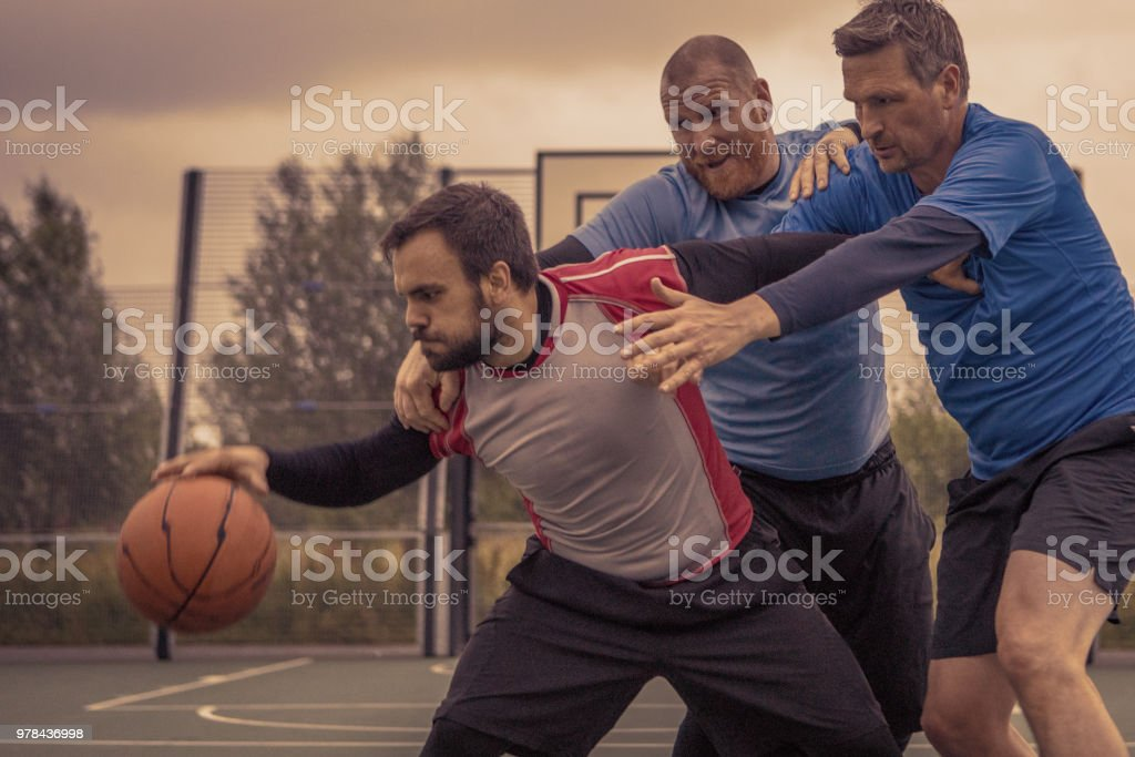 Two adult co-ed basketball teams playing a 2v2 evening pick up game on a street ball court in stock photo