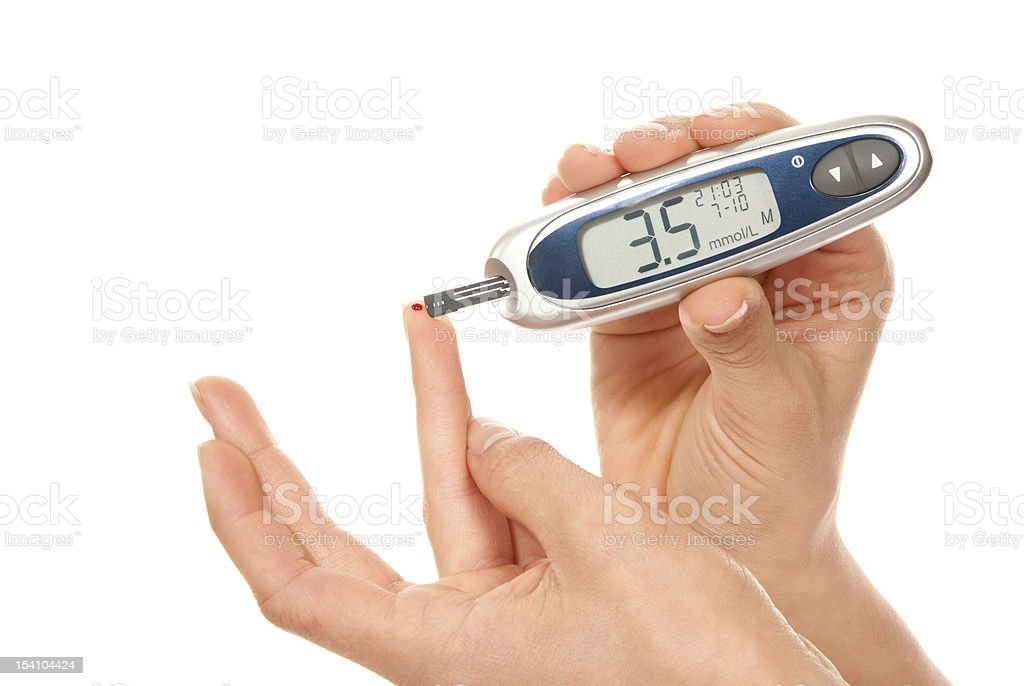 Two adult hands holding and using glucose tester royalty-free stock photo