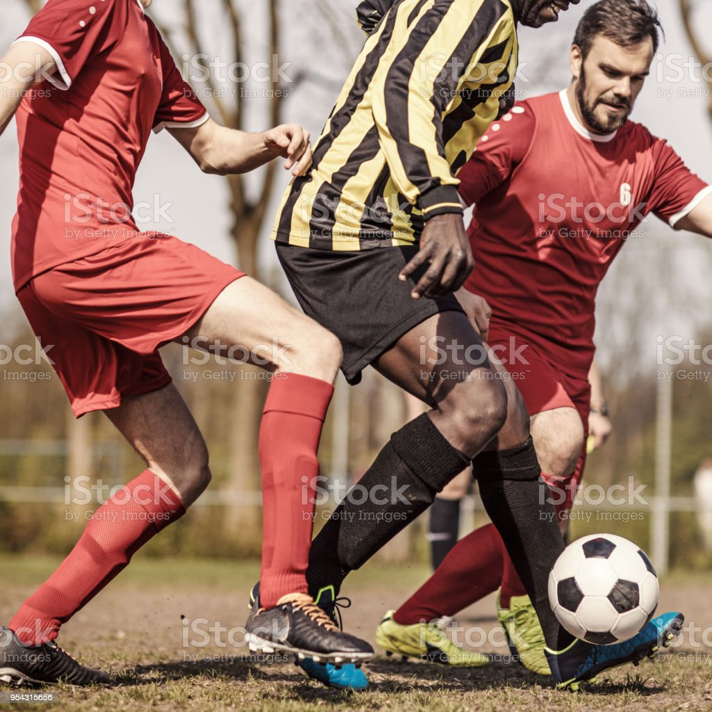 Two Adult Male Soccer Teams Competing for the ball during a match