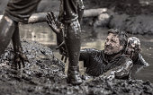 Two adult male team mates having sporty fun at a public mud run obstacle course