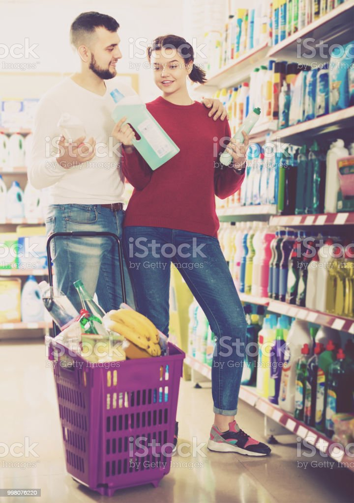 two adult people in good spirits selecting detergents in the store stock photo
