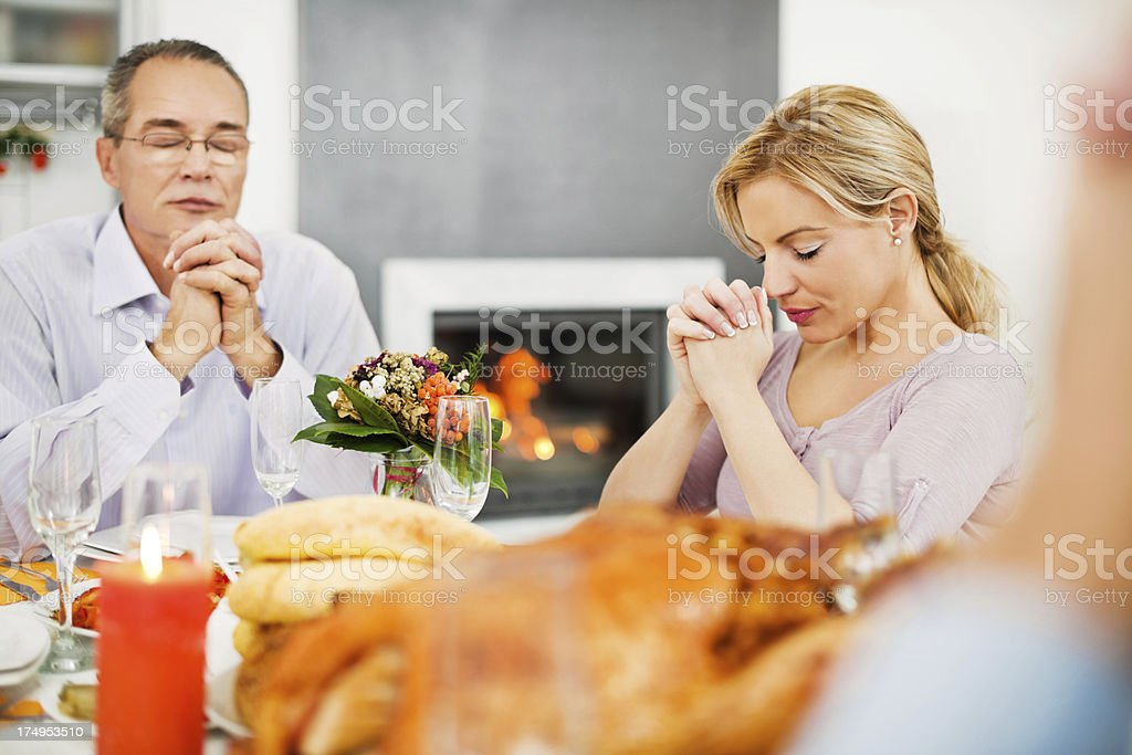 Two adult people saying their grace at Thanksgiving day. royalty-free stock photo