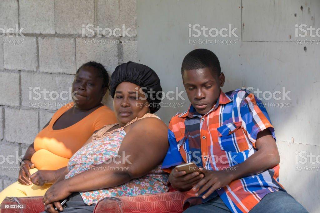 2 アダルト貧しいがっしりしたジャマイカの女性 10 代の少年で外に座っています。彼らはまだ携帯電話を持ってください。 - カリブのロイヤリティフリーストックフォト